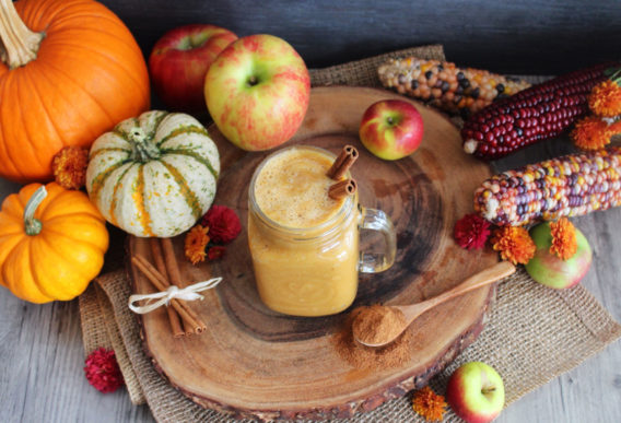 Image of apple pumpkin smoothie with festive pumpkins and indian corn
